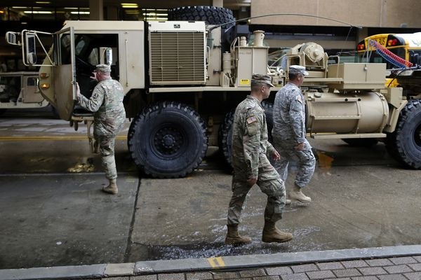 Members of the Louisiana National Guard walk past a high water vehicle at the Superdome as Hurricane Nate approaches the U.S. Gulf Coast in New Orleans, Louisiana, U.S. on October 7, 2017. REUTERS/Jonathan Bachman