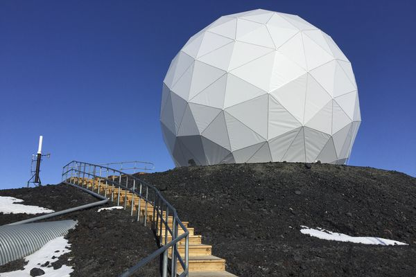 """The dome, known as the """"golf ball,"""" projects a NASA satellite dish at McMurdo Station in Antarctica, November 2016. In an era when the Trump administration is seeking to slash federal spending, the fate of Antarctic research is an open question, as the aging, inefficient buildings at McMurdo need replacing. (Jonathan Corum/The New York Times)"""