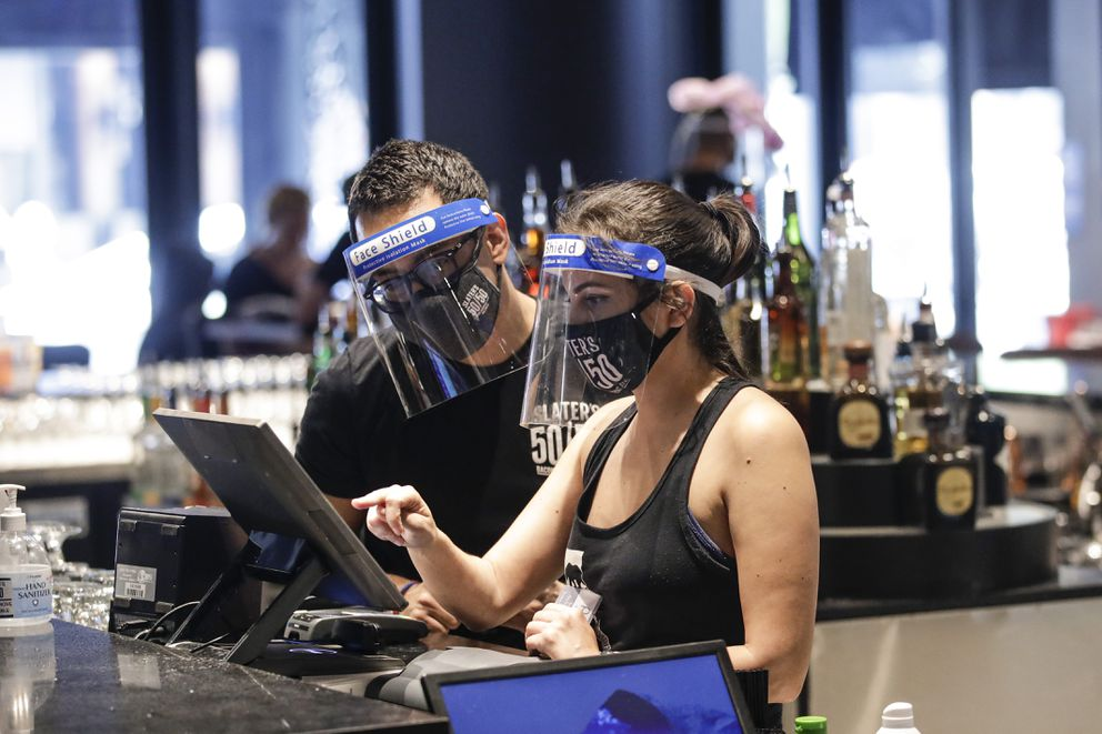 Bartenders were masks and face shields as they work at Slater's 50|50 in Wednesday, July 1, 2020, in Santa Clarita, Calif. (AP Photo/Marcio Jose Sanchez)