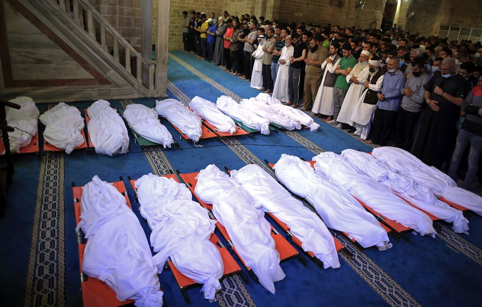 Mourners pray over the bodies of 17 Palestinians who were killed in overnight Israeli airstrikes in Gaza City, Sunday, May 16, 2021. (AP Photo/Sanad Latifa)