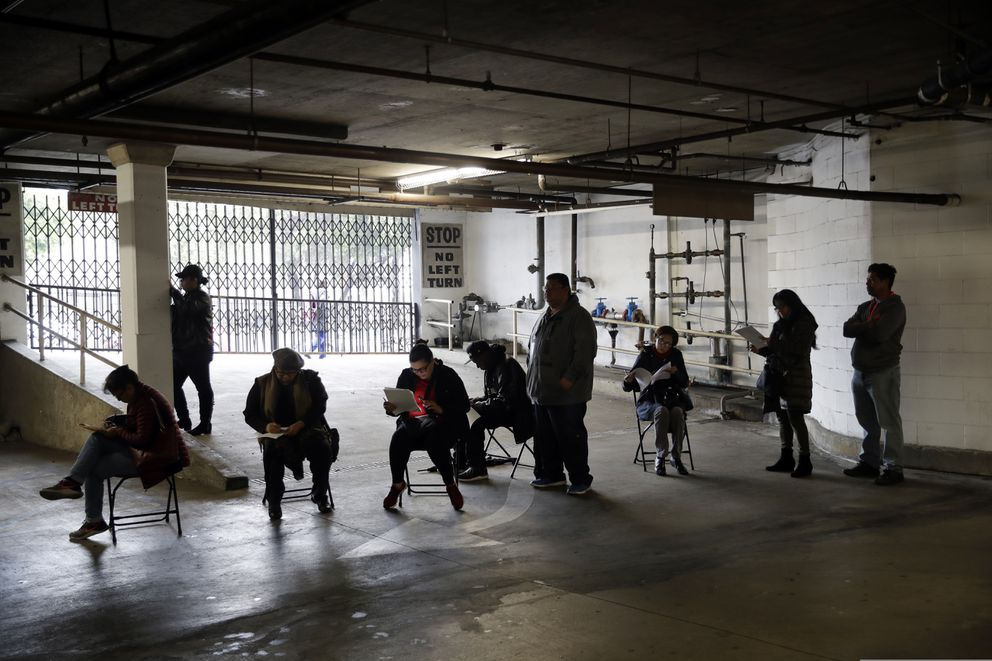 In this March 13, 2020, file photo, unionized hospitality workers wait in line in a basement garage to apply for unemployment benefits at the Hospitality Training Academy in Los Angeles. (AP Photo/Marcio Jose Sanchez, File)