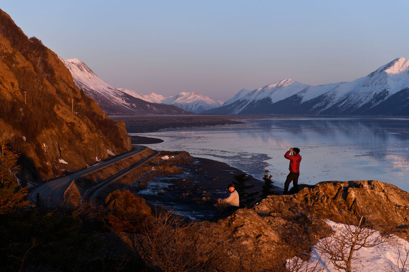 Hikers take in the view from Windy Point along Turnagain Arm at sunset on March 30, 2020. (Marc Lester / ADN)