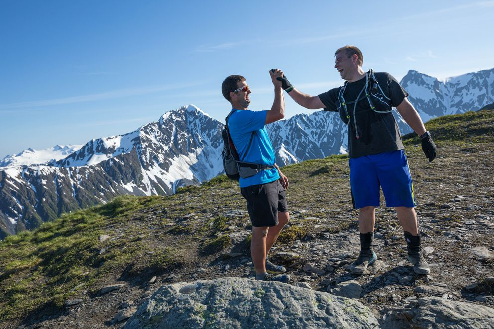 Rob Whitney, left, and Ben Schultz celebrate after reaching the top of the Mt. Marathon race course. (Loren Holmes / ADN)