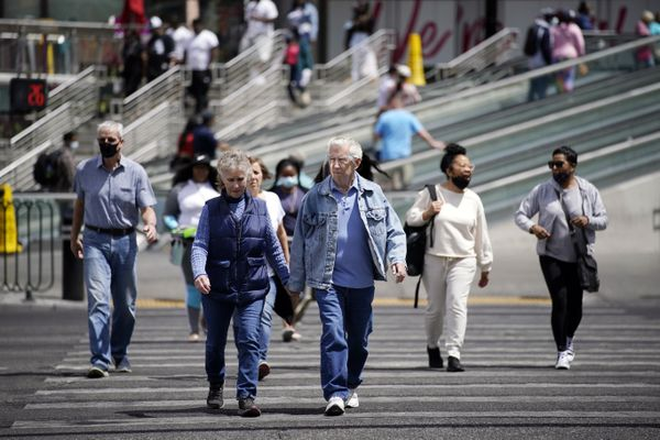 FILE - In this Tuesday, April 27, 2021, file photo, masked and unmasked pedestrians walk across Las Vegas Boulevard, in Las Vegas. Elected officials in tourism-dependent Las Vegas worried Tuesday, July 20, 2021, about public health and the economic effects of a spike in COVID-19 cases, particularly the highly contagious delta variant. (AP Photo/John Locher, File)
