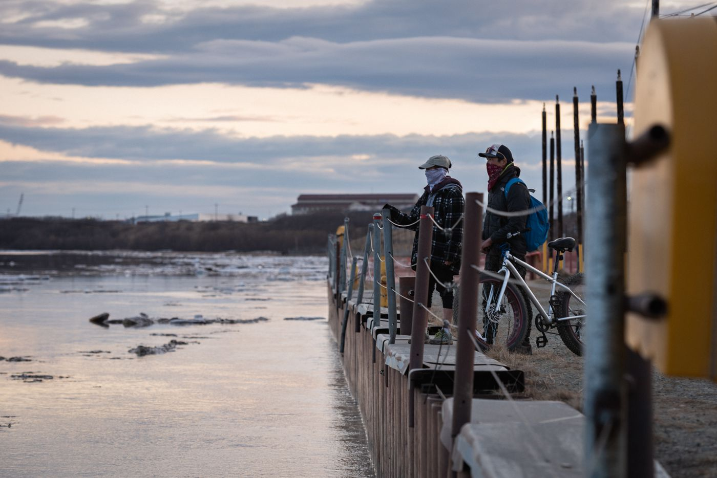 People in Bethel watch the ice flow downriver during the Kuskokwim River breakup on May 4, 2020. (Katie Basile / KYUK)