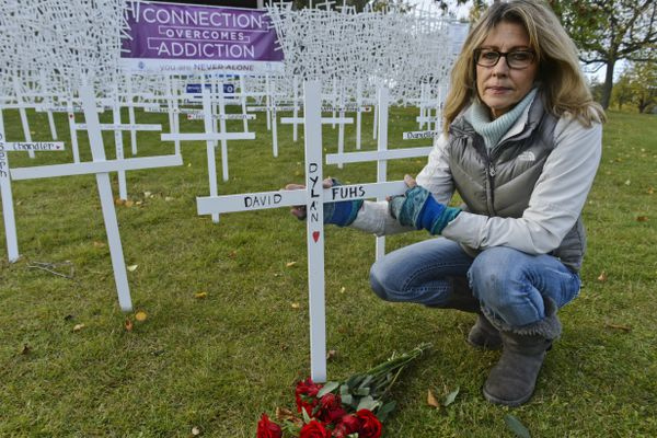 Karen Malcolm-Smith kneels by the cross memorial at the Connection Overcomes Addiction event on the Loussac Library lawn on September 18, 2020. The name of Malcolm-Smith's son, Dylan Fuhs, is written on the cross.(Marc Lester / ADN)