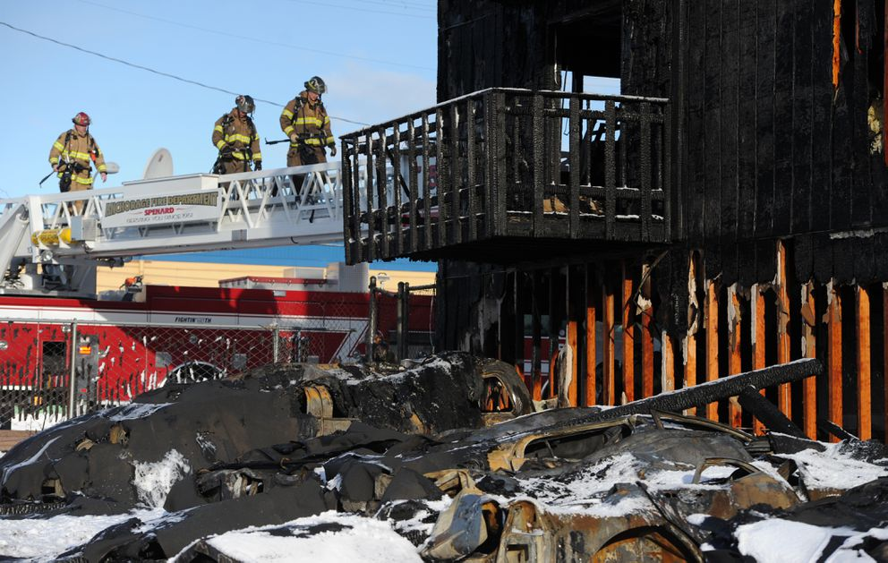 Anchorage firefighters continue their search of the Royal Suite Apartments on Wednesday, Feb. 15, 2017. Two people died, 16 were injured and dozens were displaced in a fast-spreading early morning fire in Spenard. (Bill Roth / Alaska Dispatch News)