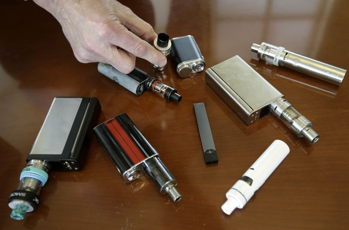 In this Tuesday, April 10, 2018 photo, Marshfield High School Principal Robert Keuther displays vaping devices that were confiscated from students in such places as restrooms or hallways at the school in Marshfield, Mass. Officials on Wednesday, August 21, 2019 said the Food and Drug Administration has joined the Centers for Disease Control and Prevention and a number of states in the investigation. of breathing illnesses among people who vape. (AP Photo/Steven Senne)