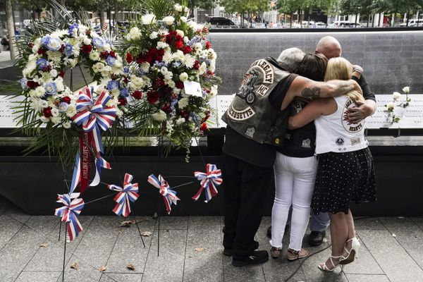 Mourners hug beside the names of the deceased Jesus Sanchez and Marianne MacFarlane at the National September 11 Memorial and Museum, Friday, Sept. 11, 2020, in New York. Americans commemorated 9/11 with tributes that have been altered by coronavirus precautions and woven into the presidential campaign. (AP Photo/John Minchillo)