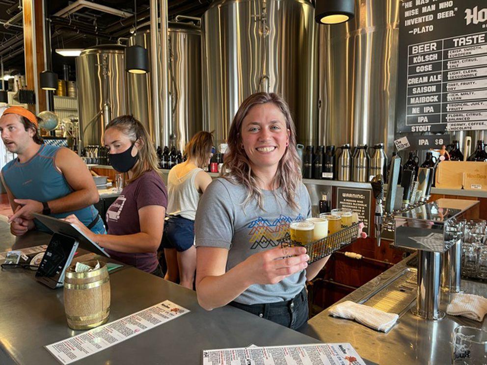 Server Ariel Ellison offers up a flight of craft beers from HooDoo Brewing, a popular brewery in Fairbanks. (Scott McMurren)