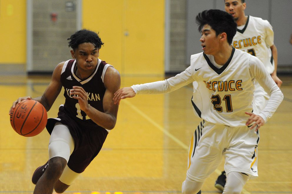 Chris Lee brings the ball down court for Ketchikan as Service junior Elijah Cano defends. (Bill Roth / ADN)