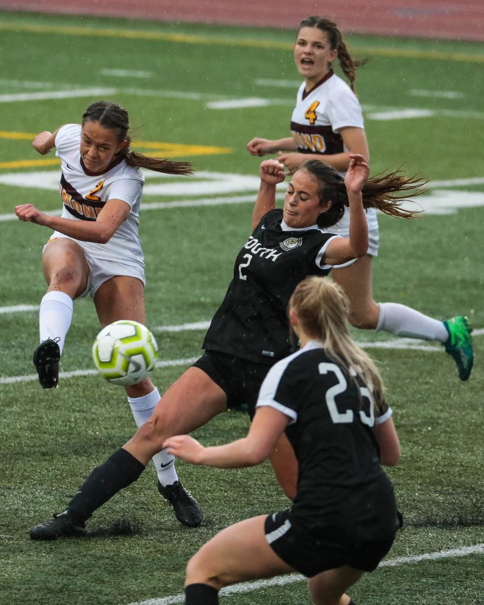 Dimond senior Madison Childers kicks the ball past South defenders Grace Chartier and Olivia Schuster. (Loren Holmes / ADN)