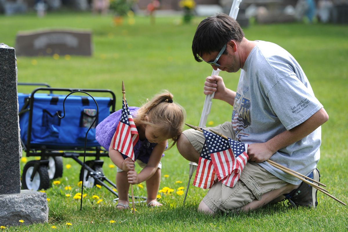 Two-year-old Dallas Pfouts and Danny Garcia, along with volunteers from the Veterans of Foreign Wars Post 1685 in Spenard, placed American flags at the graves of veterans resting in the Anchorage Memorial Park Cemetery on Sunday, May 29, 2016, in honor of Memorial Day. (Bill Roth / ADN)