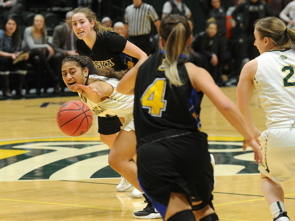 Sala Langi of UAA reaches for the ball as a pair of Nanooks converge. (Bob Hallinen / ADN)