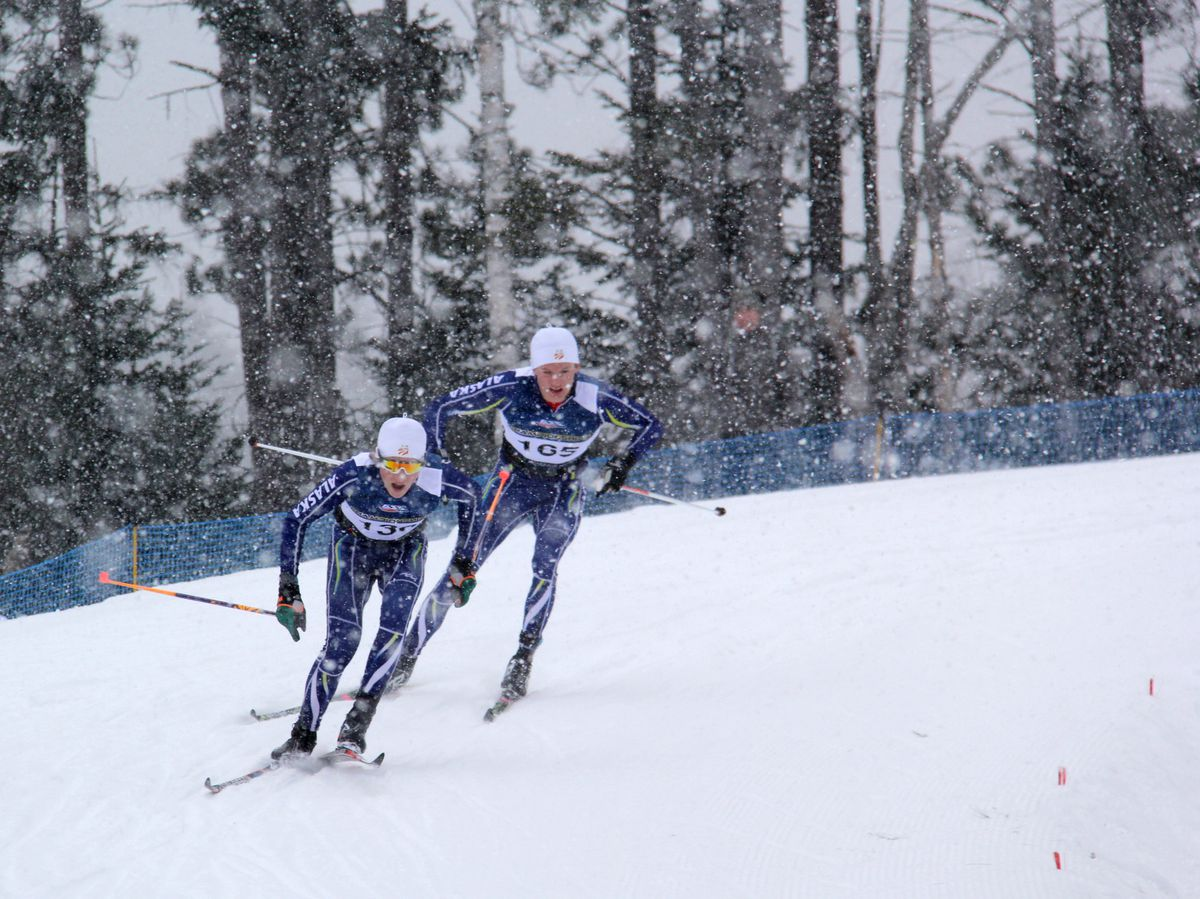 Gus Schumacher leads teammate Andrew Hull through a snow squall Friday at the U.S. Junior National nordic ski championships in Lake Placid, New York.  (Glenn Gellert / Team Alaska)