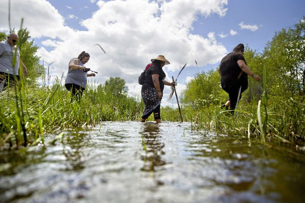 Kimberly Loring, from right, Roxanne White, Lissa Loring and George A. Hall, cross a creek looking for clues during a search for the Loring's sister and cousin, Ashley HeavyRunner Loring, who went missing in 2017 from the Blackfeet Indian Reservation in Valier, Mont., Wednesday, July 11, 2018. Kimberly has logged about 40 searches for her sister, with family from afar sometimes using Google Earth to guide her around closed roads. (AP Photo/David Goldman)