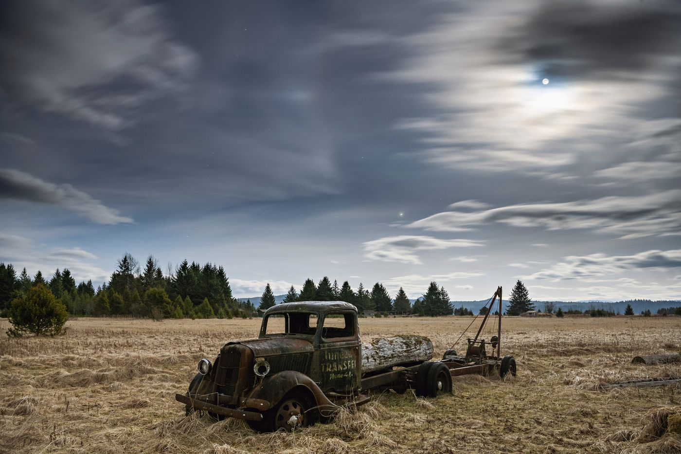 A nearly full moon illuminates the clouds and night sky above an old truck in a field on the edge of Gustavus, Alaska, April 2018. The tiny town serves as the gateway to Glacier Bay National Park. (Christopher Miller/The New York Times)
