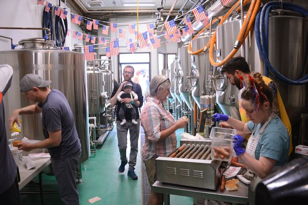 Employees of Devil's Club Brewing in Juneau, Alaska serve hot dogs between the brewery's tanks on Sunday, July 4, 2021. The brewery is located on the route of the Fourth of July parade in Alaska's capital city. (James Brooks / ADN)