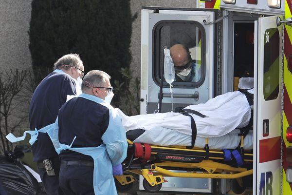 A person is loaded into an ambulance, Thursday, March 12, 2020, at the Life Care Center in Kirkland, Wash., near Seattle. The nursing home is at the center of the outbreak of the COVID-19 coronavirus in Washington state. For most people, the new coronavirus causes only mild or moderate symptoms. For some it can cause more severe illness, especially in older adults and people with existing health problems. (AP Photo/Ted S. Warren)