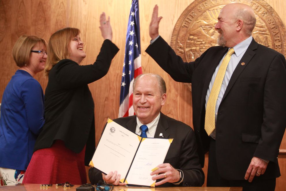 Anchorage Republican Sen. Mia Costello hi-fives Fairbanks Democratic Rep. Adam Wool after Alaska Gov. Bill Walker signed legislation to allow ride hailing companies like Uber and Lyft to operate in the state. Costello and Wool each sponsored versions of the legislation, which Walker signed Thursday, June 15, 2017 at the Capitol in Juneau. (Nathaniel Herz / Alaska Dispatch News)