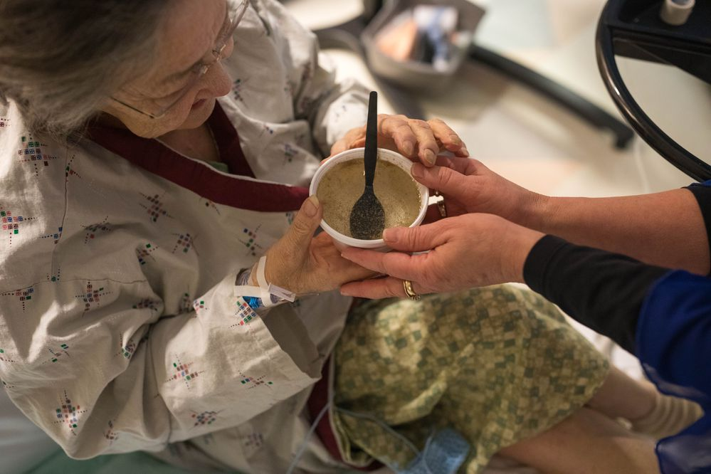 Food service manager Londa Shahan offers a cup of seal soup broth to Jean Hull, a patient at the Alaska Native Medical Center hospital, on Tuesday, Jan. 22, 2019. The seal meat, one of a number of different traditional Native foods offered each Tuesday, was donated by a subsistence hunter in Ketchikan.