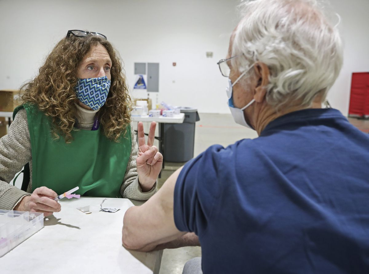 Public Health Nurse Karrin Parker talks with James Courtney about how to schedule his second dose of the Moderna COVID-19 vaccine before receiving his first dose at a vaccine clinic at the Alaska State Fairgrounds in Palmer on Tuesday, Jan. 12, 2021. (Emily Mesner / ADN)