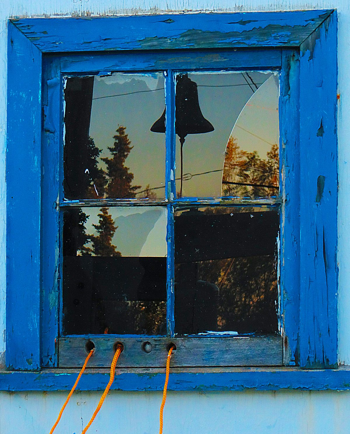 Early morning light is reflected in the fractured bell-ringer's window at the Transfiguration of Our Lord Russian Orthodox Church in Dillingham in September 2013. (Clark Fair)