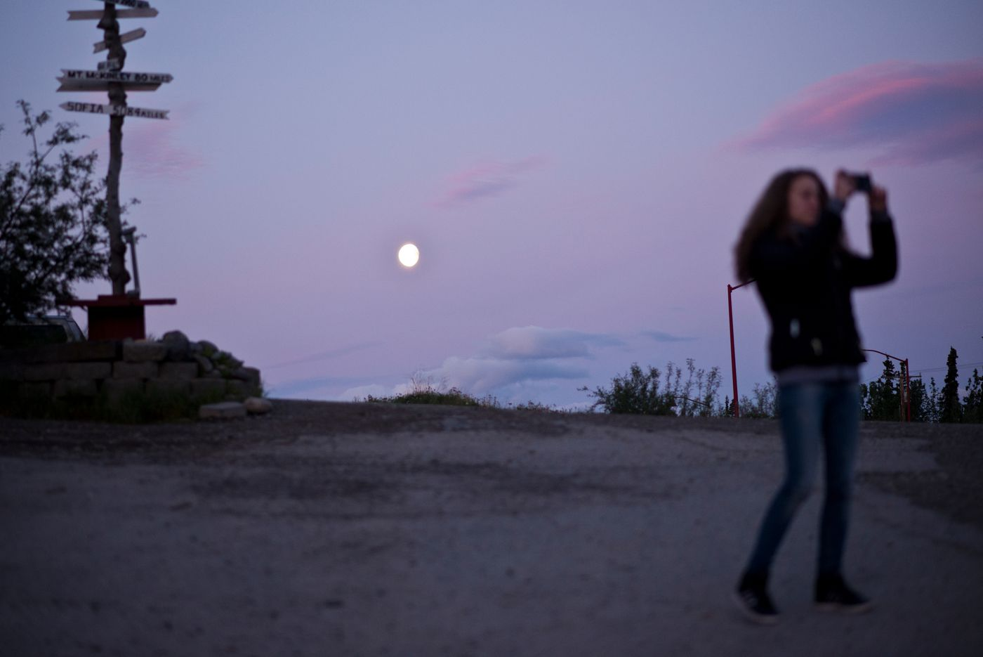 Before boarding a shuttle bus back to employee dorms, a woman takes a picture at about 2:30 a.m. Thursday, June 23, 2016. The event is one of the few social outing for many J-1 visa students who work multiple jobs in the business district outside Denali National Park. (Marc Lester / Alaska Dispatch News)