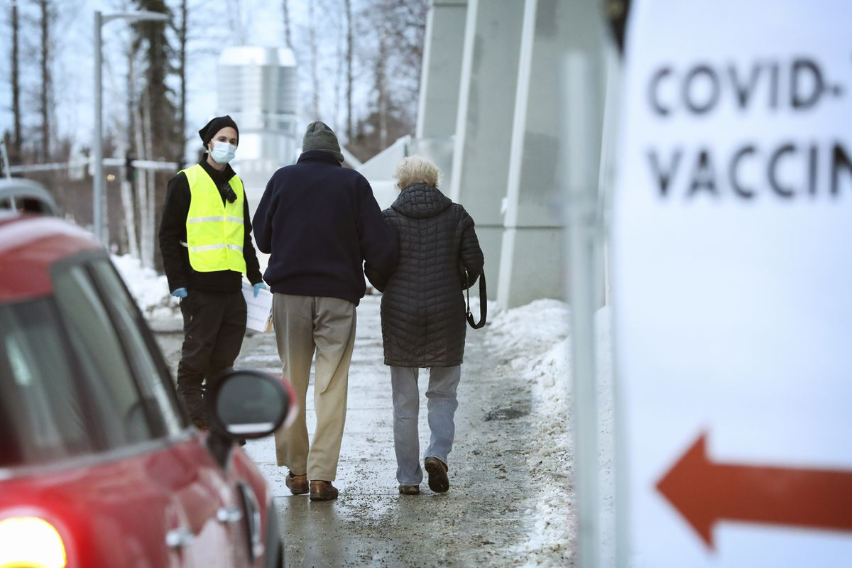 A man and woman walk to the patient drop-off area outside the Alaska Airlines Center for a scheduled appointment to receive the Pfizer-BioNtech COVID-19 vaccine in Anchorage on Saturday, Jan. 9, 2021. (Emily Mesner / ADN)