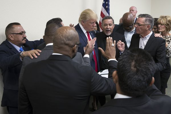 Donald Trump bows his head as Pastor Paul Marc Goulet, center, leads a prayer at the International Church of Las Vegas, Oct. 5, 2016. Trump met with church pastors here and vowed that if elected he would strike down the Johnson Amendment, which restricts churches and other non-profit organizations from endorsing political candidates. (Stephen Crowley / The New York Times)