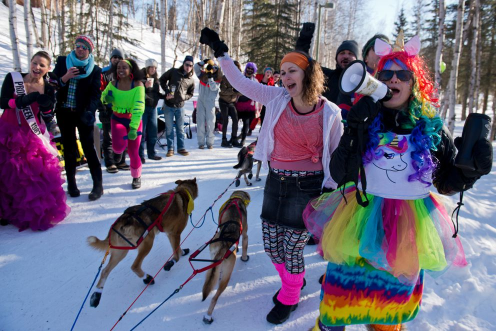 A 1980s prom-themed party greets mushers on the Chester Creek Trail. Karie Vix is at right and Christina Colvin second from right during the ceremonial start of the 2017 Iditarod. (Marc Lester / Alaska Dispatch News)