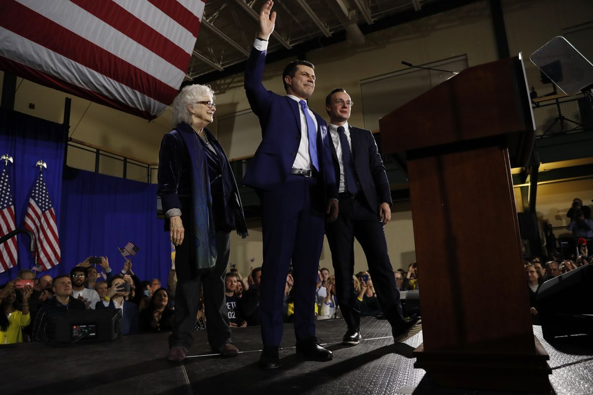 Democratic presidential candidate former South Bend, Ind., Mayor Pete Buttigieg, center, his husband Chasten Buttigieg, right, and his mother Anne Montgomery, stand on stage together as supporters cheer at a primary night election rally at Nashua Community College, Tuesday, Feb. 11, 2020, in Nashua, N.H. (AP Photo/Andrew Harnik)