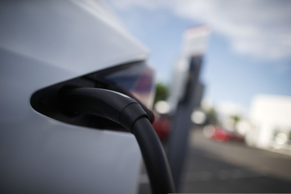 A Tesla car is plugged into a charging station at a dealership in Littleton, Colo. (AP Photo/David Zalubowski, File)