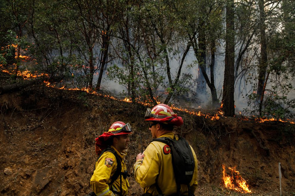 Firefighters watch a fire burn along the slope on Highway 29 in Calistoga, Calif., on Thursday, Oct. 12, 2017. (Marcus Yam/Los Angeles Times/TNS)