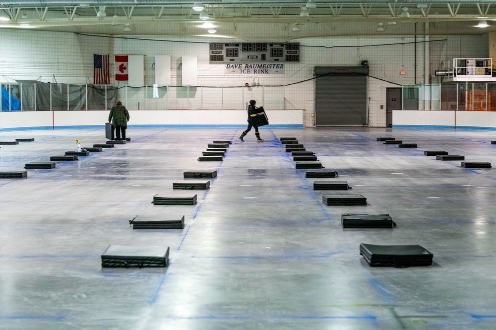 Beans Cafe employee Ruth Free, left, and deputy director Kim Kovol lay out sleeping mats at the Ben Boeke Ice Arena on Friday. (Loren Holmes / ADN)