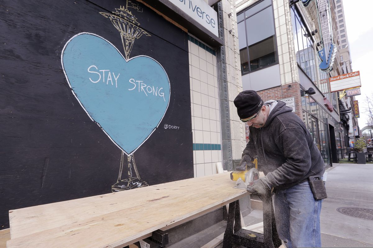 A carpenter, who declined to be identified, cuts plywood to cover a closed store where artwork in support of people affected by the coronavirus already covers an adjacent panel in downtown Seattle, Thursday, April 2, 2020. (AP Photo/Elaine Thompson)