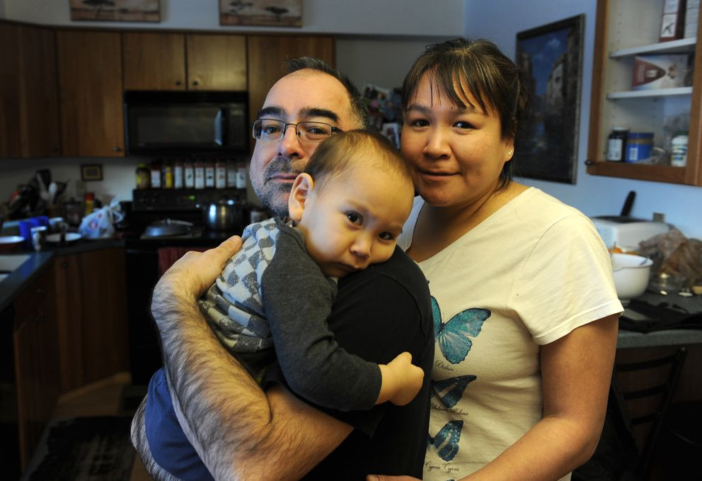 Christopher Hale and Kimberly Pingayak pose for a photograph with their first grandchild, Leo Night, in their South Anchoragehome Saturday. (Bob Hallinen / ADN)