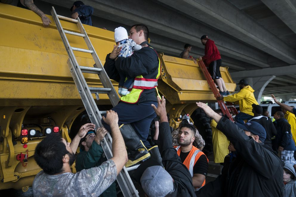 People are unloaded after being rescued by a large truck along Tidwell Road near toll road 8 in Houston. Washington Post photo by Jabin Botsford