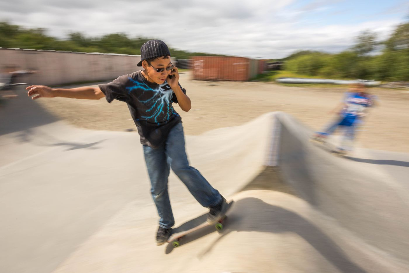 Ethan Nicolai, 13, talks to a friend on his cell phone as he skateboards at the Kwethluk skate park on Friday, August 7, 2015. The park, which was built with an Indian Health Services grant, is the only one of its kind in a small rural Alaska village. (Loren Holmes / ADN)