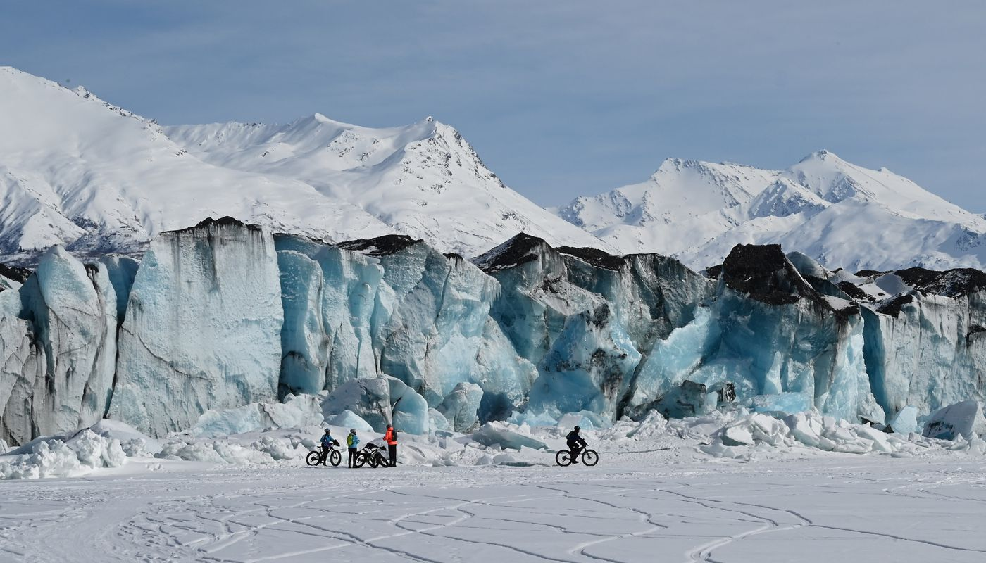 Bike riders enjoy the view close to the face of Knik Glacier, Wednesday, March 24, 2021. Visitors to the area should always be aware of their surroundings and to understand that a glacier is a moving, dynamic force. (Anne Raup / ADN)