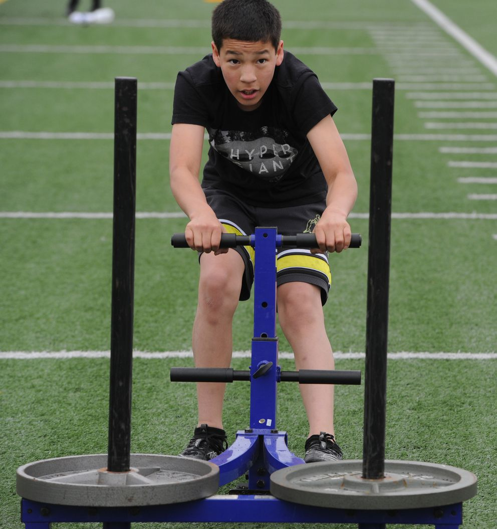 South High Wolverines freshman Joe Weber-Thomas pulls a sled as the defending state champions took to the field for high intensity interval training on the first day of football practice on Monday, June 8, 2020. (Bill Roth / ADN)