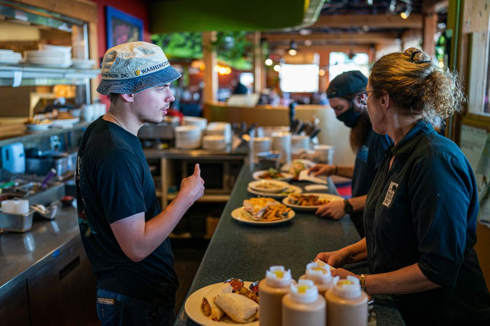 Expediter Dalton Roullier, left, talks with server Loni Laurent as she pick up an order at the Bear Tooth Grill on Friday, June 11, 2021. Bear Tooth Theatre Pub and Grill general manager Steph Johnson says the restaurant has been struggling to hire enough staff to fully re-open their indoor dining areas. (Loren Holmes / ADN)