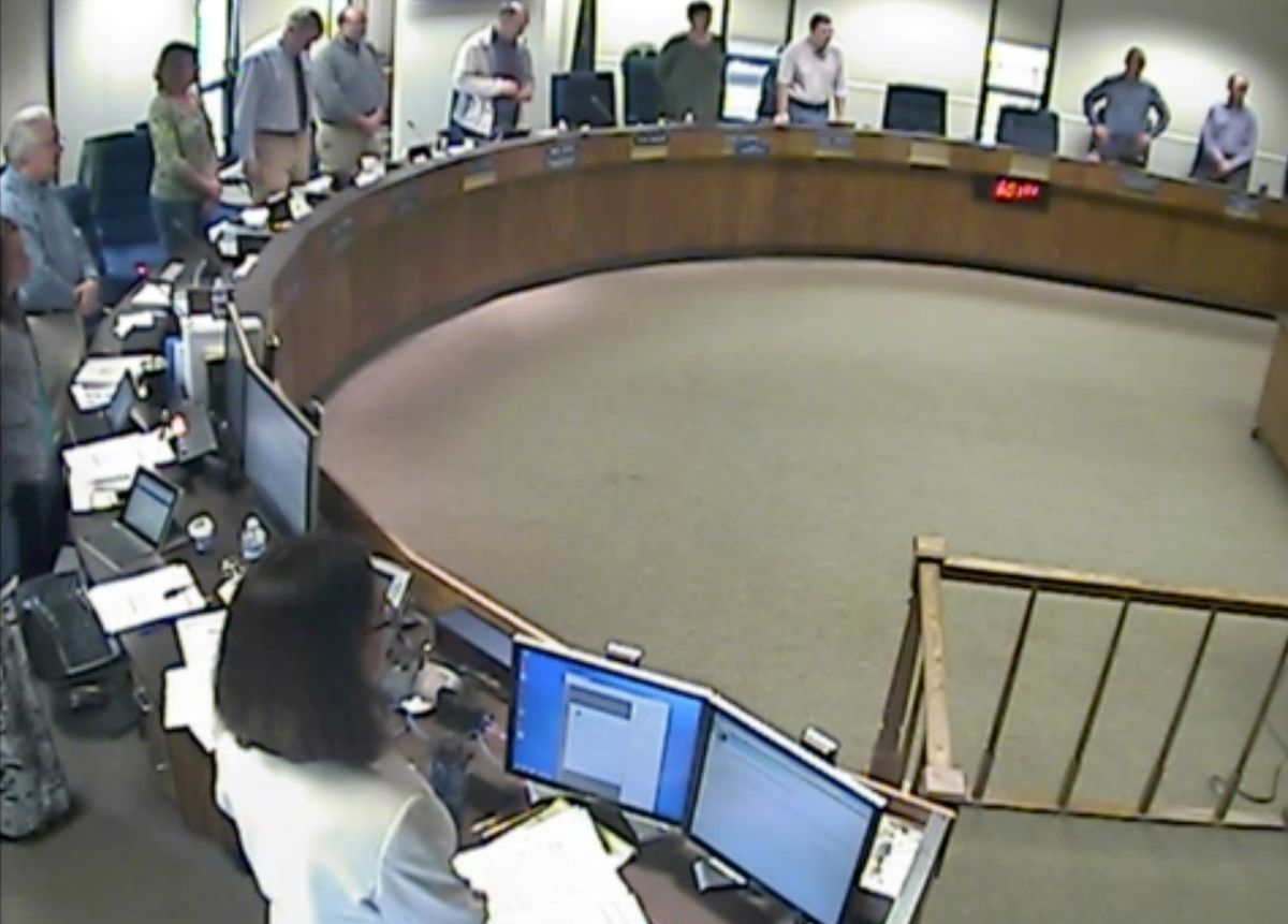 Members of the Kenai Borough Assembly stand during the invocation at the start of the Aug. 9 meeting. (Screengrab from Kenai Borough video)