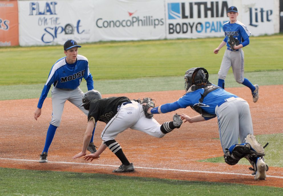 Palmer catcher Skyler Hale (right) tags out South's Josh Costello during a failed squeeze play as third baseman Alasdair McKechnie looks on. (Matt Tunseth/Alaska Star)
