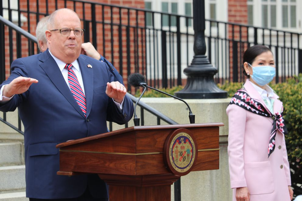 Maryland Gov. Larry Hogan speaks at a news conference on Monday, April 20, 2020 in Annapolis, Md., with his wife, Yumi Hogan, right, where the governor announced Maryland has received a shipment from a South Korean company to boost the state's ability to conduct tests for COVID-19 by 500,000. Hogan said he asked his wife, who is Korean, to help negotiate with Korean officials, on March 28, and that set in motion 22 days of vetting and negotiations to bring the large increase in testing capacity to Maryland. (AP Photo/Brian Witte)
