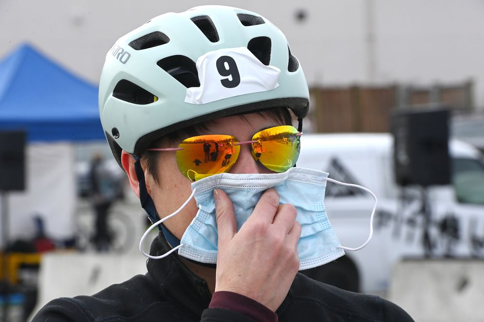 Victoria Oxentenko holds up a mask while waitng in line to start during the Bike for Women at Chugiak High School on Sunday, May 2, 2021. (Bill Roth / ADN)