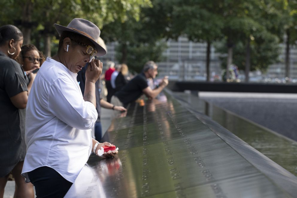 A woman wipes away tears as she stands next to the north pool prior to a ceremony marking the 18th anniversary of the attacks of Sept. 11, 2001 at the National September 11 Memorial, Wednesday, Sept. 11, 2019 in New York. (AP Photo/Mark Lennihan)
