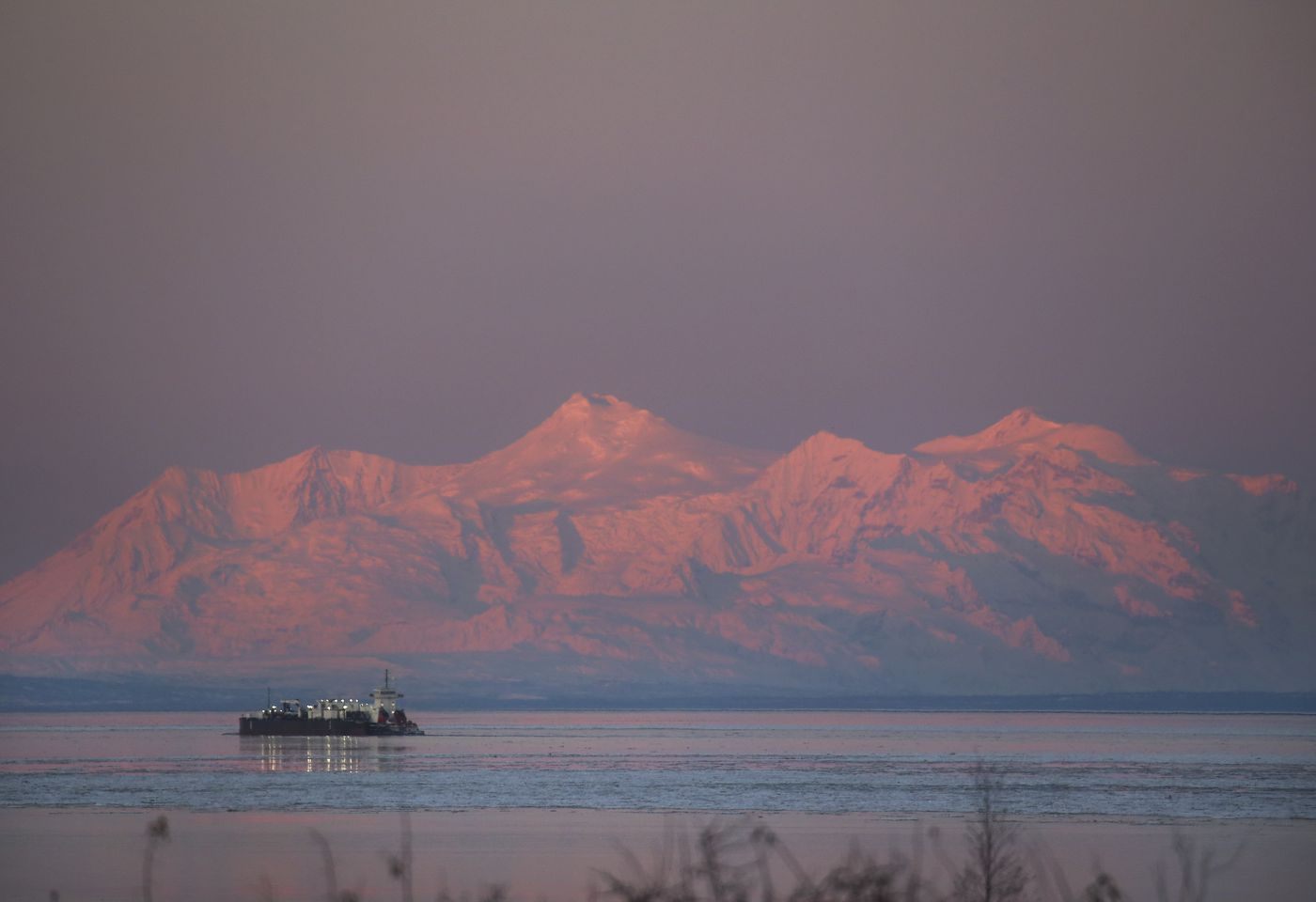 NOVEMBER 9. The articulated Tug-Barge Aveogan/Oliver Leavitt moves south along the Knik Arm after departing Port of Alaska around 8:25 a.m. as the sun rises, highlighting the Tordrillo Mountains. (Emily Mesner / ADN)