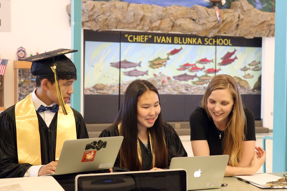 Meghan Redmond, right, assistant principal at Chief Ivan Blunka School in New Stuyahok, helps students Blunka Blunka Jr. and Daria Gust with edits to their graduation speeches in May 2018. (Photo by David Piazza)