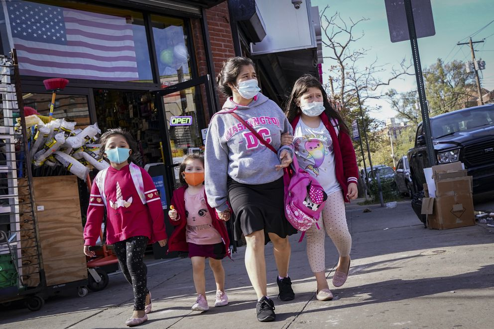 Pedestrians in masks pass a store on Thursday, Oct. 15, 2020, as government restrictions on business activity limit operations due to an increase of COVID-19 cases, in the Far Rockaway neighborhood of the borough of Queens in New York. After shutdowns swept entire nations during the first surge of the coronavirus earlier this year, some countries and U.S. states are trying more targeted measures as cases rise again around the world. (AP Photo/John Minchillo)